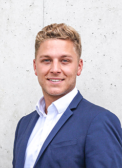 Das Bild zeigt einen jungen Mann vor einer Betonwand.