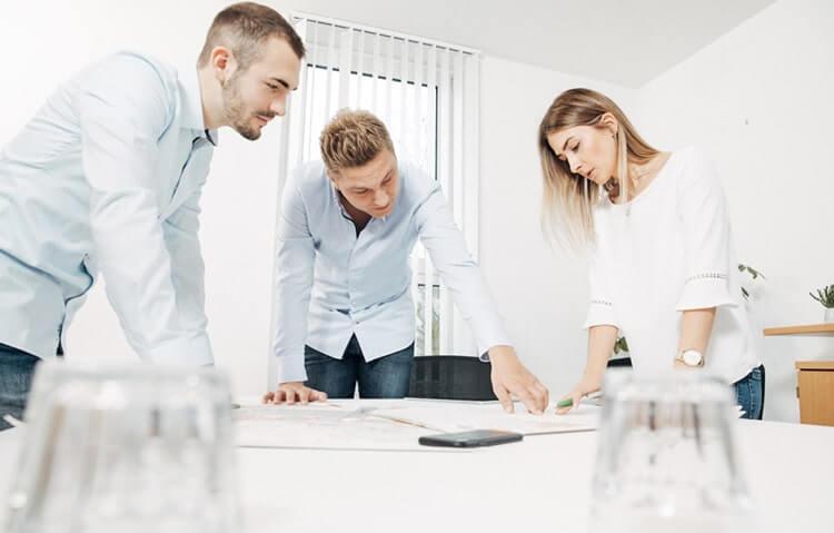 Auf dem Bild sind drei Makler zu erkennen welche gerade ein Neubauprojekt in Schwabach planen.